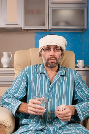 mature sick man sitting in chair with tablets Stock Photo - 17395022
