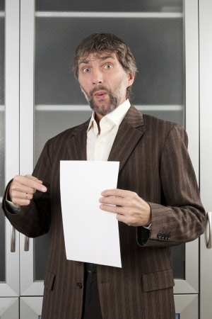 surprised man in business suit shows blank sheet of paper Stock Photo - 17277984