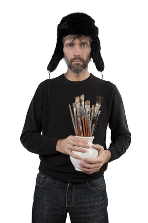 adult man in hat ear flaps holding jug with brushes isolated white Stock Photo - 17277976
