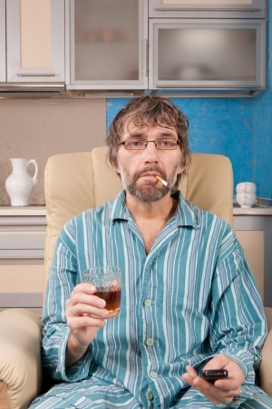 mature drunk man sitting in chair watching tv with glass and cigarette photo