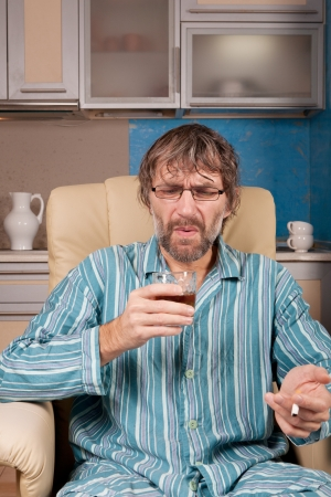 mature drunk man sitting in chair with glass and cigarette photo