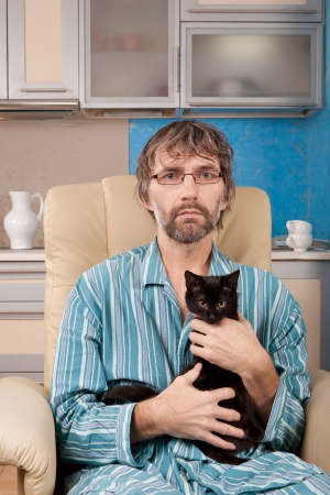 mature man sitting in chair with kitten Stock Photo - 17277981