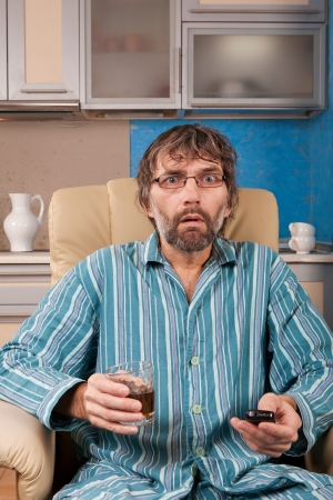 mature drunk man sitting in chair watching tv with glass and remote photo