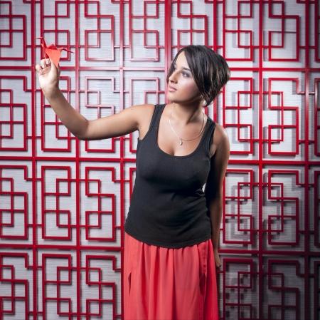 muchacha hermosa que sostiene gr�a de celos�a sobre papel rojo Foto de archivo