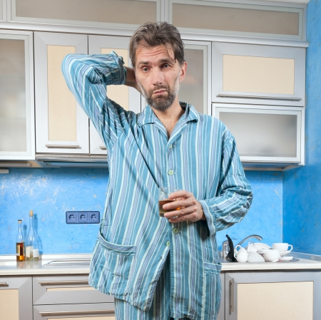 mature drunk man standing in pajamas with glass photo
