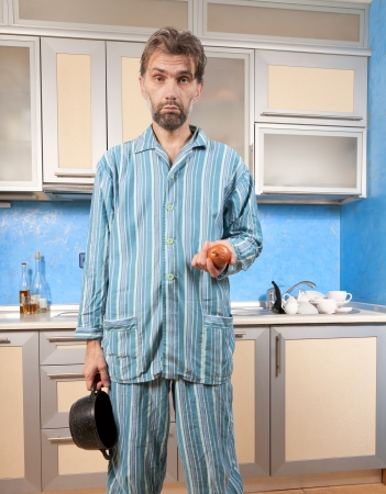 mature drunk man standing in pajamas with onion photo