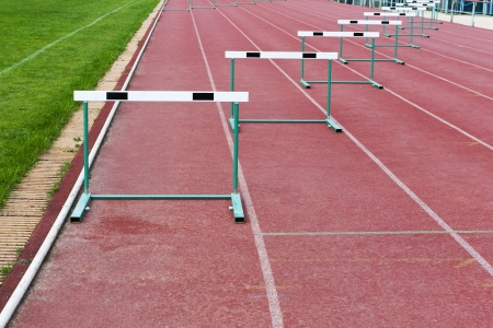 straight lanes of red cinder running track with barriers