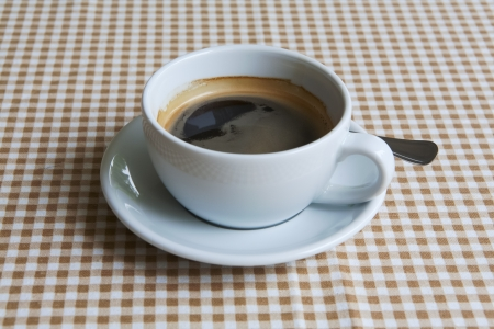 cup of black coffee on table dressed with tablecloth Stock Photo