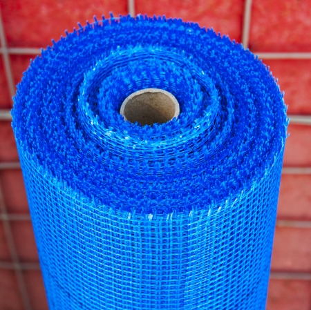 roll of blue plastic mesh on red background Stock Photo