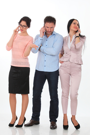 businessgroup: Photo of two women calling by phone with business man between them