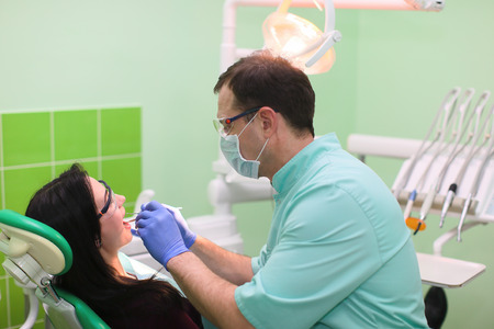stomatologist: close up of dentists and assistant with mirror, drill and dental air water gun spray treating female patient teeth at dental clinic Stock Photo
