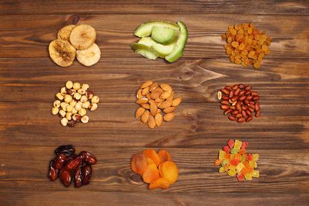 frutas deshidratadas: frutas y nueces secas en el fondo de madera. Foto de archivo