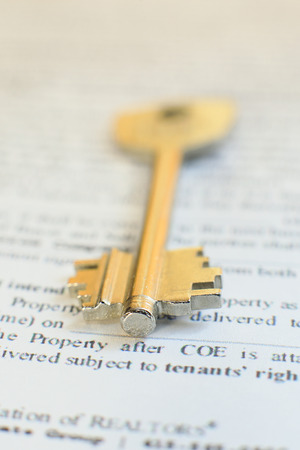 financial official: house key lying on a contract of house sale lease insurance or mortgage in a real estate concept viewed low angle with focus to the tip.