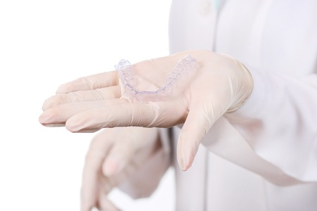 Close-up shot of doctors hands in gloves holding silicone mouth guard. Teeth care Stock Photo