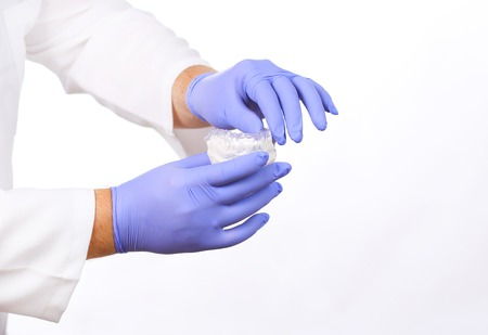 doctor holding gift: Close-up shot of doctors hands in gloves holding silicone mouth guard.