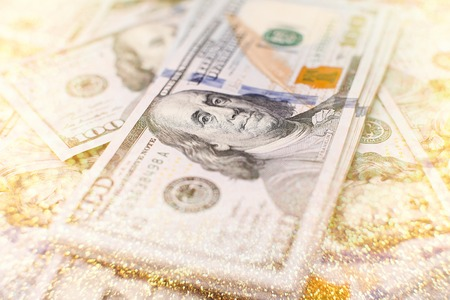 A stack of money. Heap of one hundred dollar bills on money background. Fake money. Shallow depth of field. Selective focus. Stock Photo