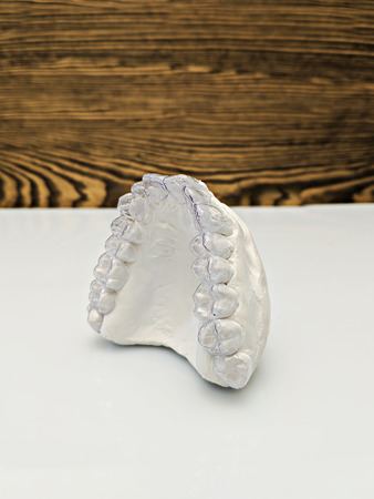 Close-up individual tooth tray Orthodontic dental theme. In hand Invisible braces