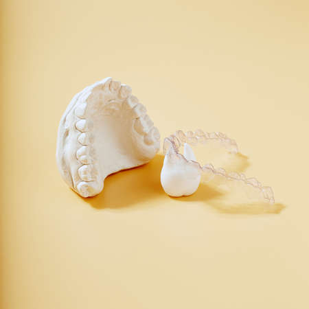 Orthodontic dental theme on yellow background.Transparent invisible dental aligners or braces aplicable for an orthodontic dental treatment