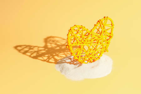 Heart in sand on yellow background, concept with shadow