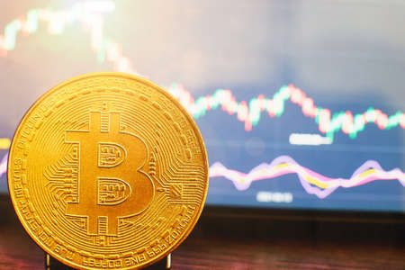 Bitcoin chart on-screen among piles of Bitcoins. Bitcoin trading concept.