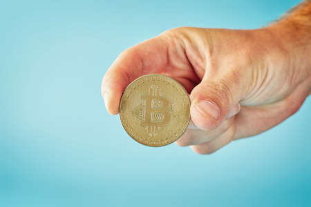 Man holding in hand symbol of crypto currency - electronic virtual money for web banking and international network payment, selective focus, toned Stock fotó