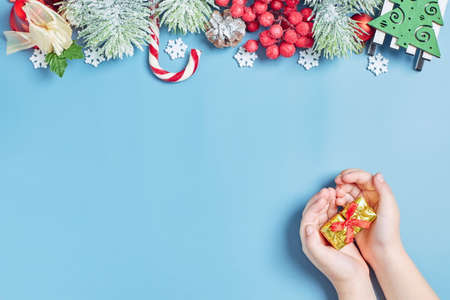 Girl holding a gift on a New Year's background. Children are waiting for gifts, Christmas tree lights, pine branches, red winter berries and snow. Top view.
