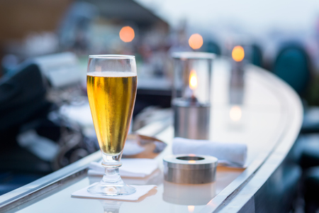 Glass of beer in Bangkok city view point from rooftop of building, blue sky and city light, Bangkok is the most populated city in Southeast Asia. Bangkok , Thailand