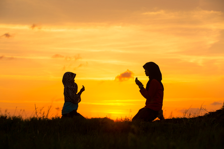 Muslim girls silhouette blurred background,Silhouettes,the light of faith, hope, faith, supplication,Hand of Muslim people praying with mosque interior background, Stock Photo