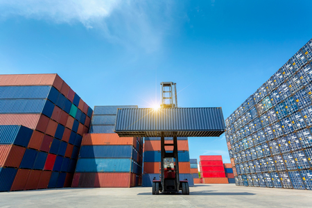 Forklift truck lifting cargo container in shipping yard or dock yard against blue sky with cargo container stack in background for transportation import,export and logistic industrial concept