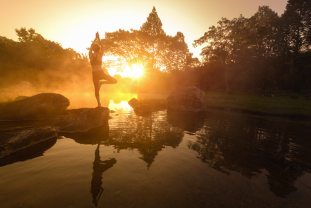 Asian Young woman doing yoga in morning park,Woman Yoga relax in nature,Asian woman is practicing yoga at mountain lake