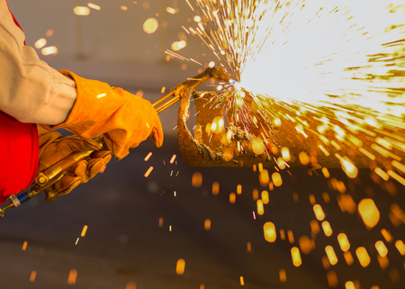 Asian worker cutting steel pipe by using metal torch and install roadside fence