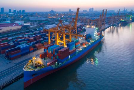 Luftaufnahme des Geschäftshafens mit Landkran-Ladecontainer im Containerschiff im Import / Export und in der Geschäftslogistik mit Kran und Versandfracht. Internationales Transportkonzept.