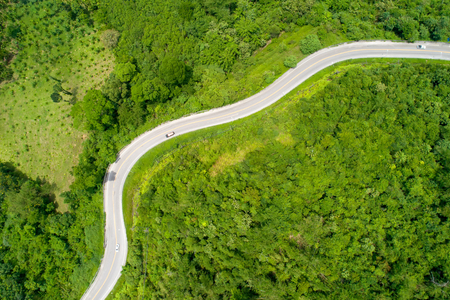 Aerial from drone cars are going through a curves road on mountain. The highway road across a mountain