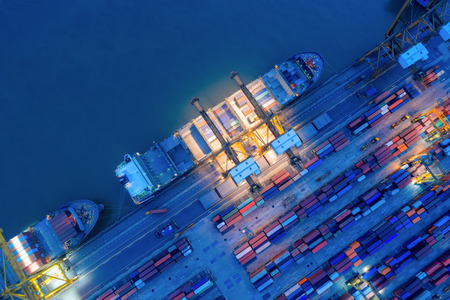 Aerial view of business port with shore crane loading container in container ship in import/export and business logistics with crane and shipping port .International transportation and port concept.