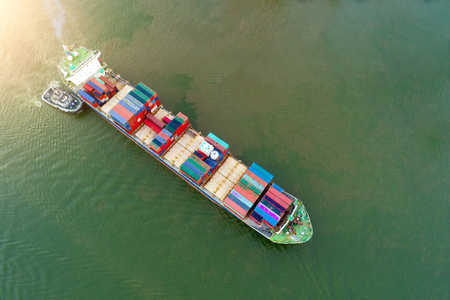 Aerial view of business port with shore crane loading container in container ship in import/export and business logistics with crane and shipping port cargo.International transportation and port concept.