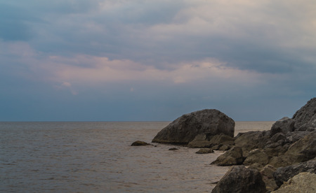 tinge: Evening sky, calm sea with a pinkish tinge and rocks on the shore Stock Photo