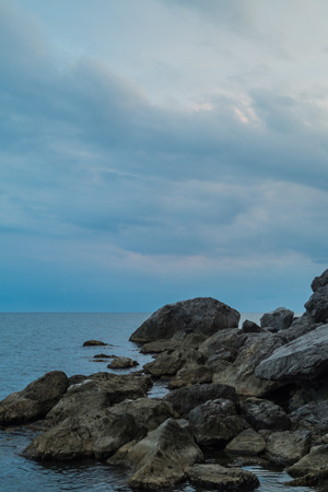 clouds making: Stones on the sea and sky with clouds making their way to the sun Stock Photo