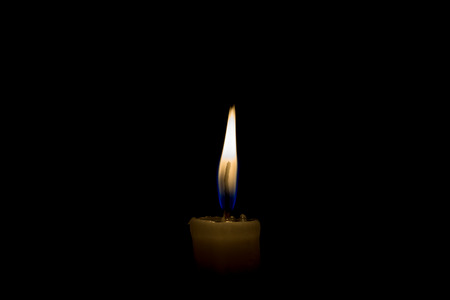 lit candle: A lit candle wax in the dark in the house