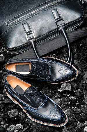 Close-up view of the stylish and elegant black leather men's dress shoes and a bag for business meetings. Stock Photo