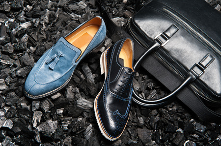 Close-up view of the stylish and elegant black leather mens dress shoes and a bag for business meetings.