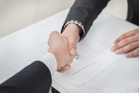 Top deal! Young businessmen shaking hands with each other in the business center. Successful businessmen on a corporate meeting close-up view Standard-Bild