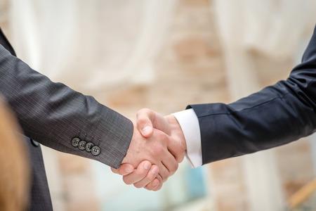 buen trato: Buen negocio! Dos j�venes de negocios de pie uno frente al otro y darles la mano. Los j�venes sonriendo a la c�mara. Close-up ver a continuaci�n