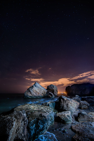 Stars and mystical sea cliffs. Night view of the sea cliffs under the night sky. Shining stars and a full moon and the Milky Way. Aside sparkles night city metropolis. photo