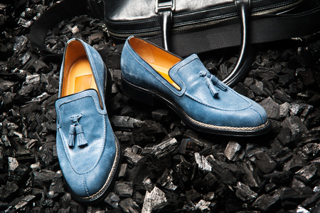 Close-up view of the stylish and elegant blue or blue suede leather men's dress shoes and a bag for business meetings.