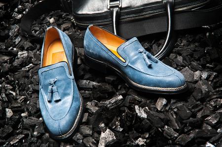Close-up van de stijlvolle en elegante blauw of blauwe suède mannen kleding schoenen en een tas voor zakelijke bijeenkomsten.