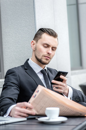 Missed call. Young man in formal wear holding a phone at the same time reading the newspaper photo