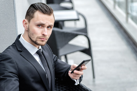 Telephone in business. Young man in formal wear holding a phone and looks straight into the camera. photo