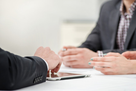 office wear: Solving problems! Hands of three and two businessmen discussing business affairs. Successful businessmen discussing business on a tablet. Couple man and woman sitting at the table. Close up arms