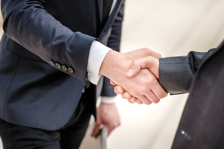 Good deal! Two young businessman standing opposite each other and shake their hands. Young people smiling into the camera. Close-up view below