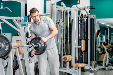 loads: Preparing for power exercises. Young and handsome athletic man loads trainer in the gym looking at dumbbell. Stock Photo